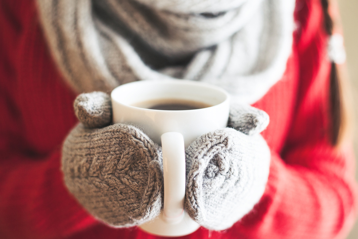 Woman hands in gloves holding a mug